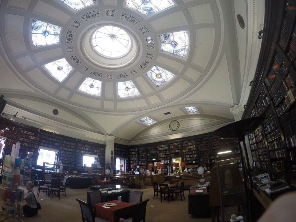 The upstairs room of Manchester's Portico Library showing the book shelves, cupola and people reading