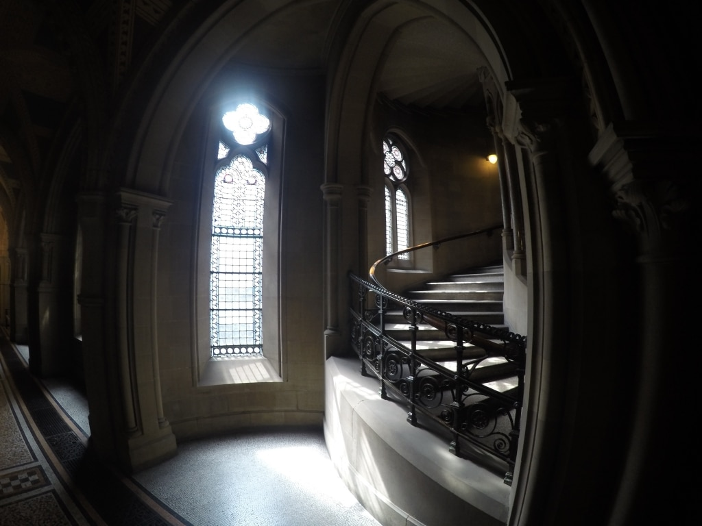 A dark winding staircase next to a Gothic arch window
