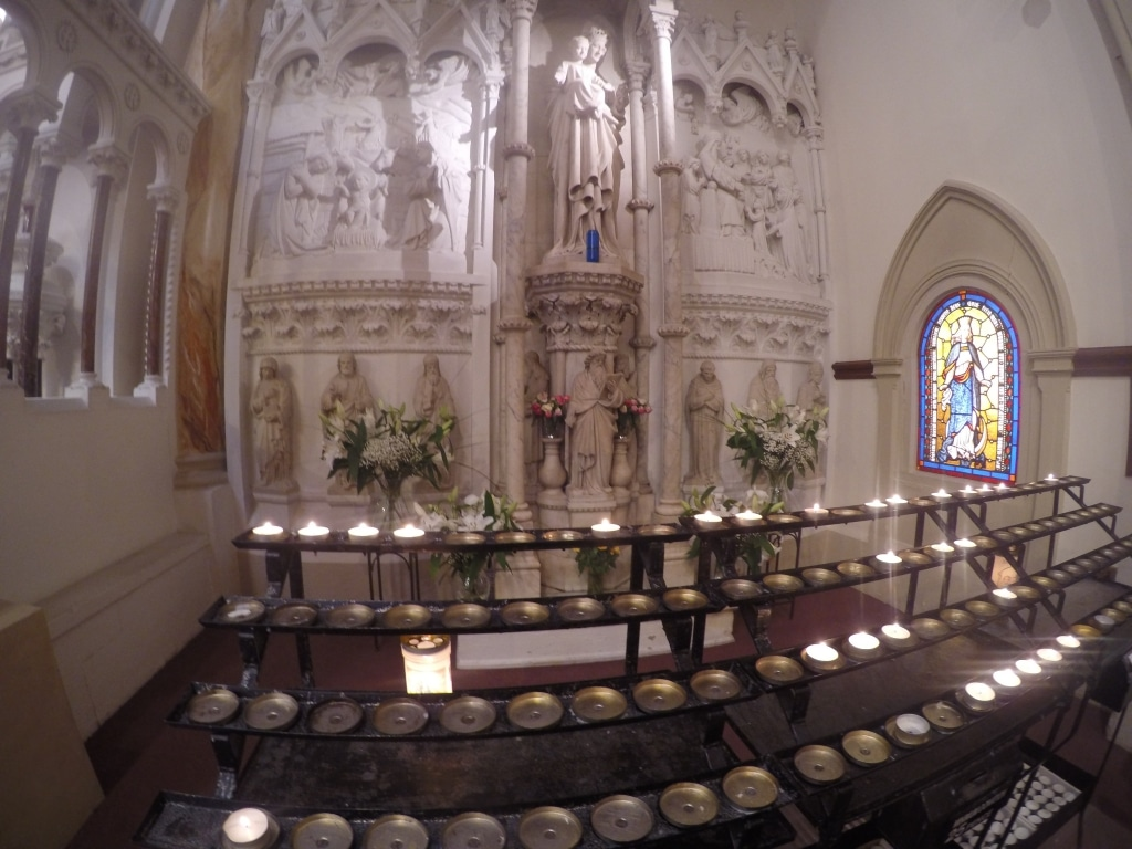 Rows and rows of candles, some lit, others not, in front of a shrine to Saint Mary