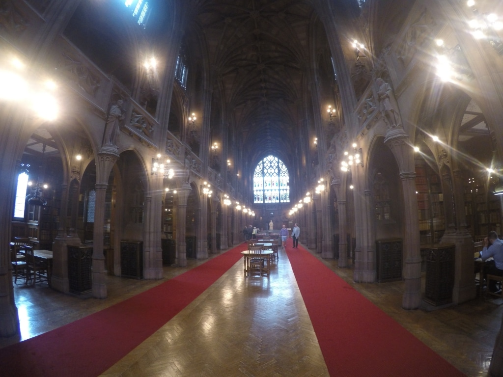 The interior of the main hall in The John Ryland Library showing Gothic arches and a stained glass window