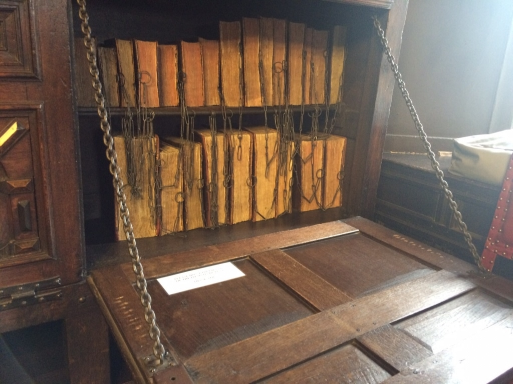 Extremely old books chained together in a pull down bureau