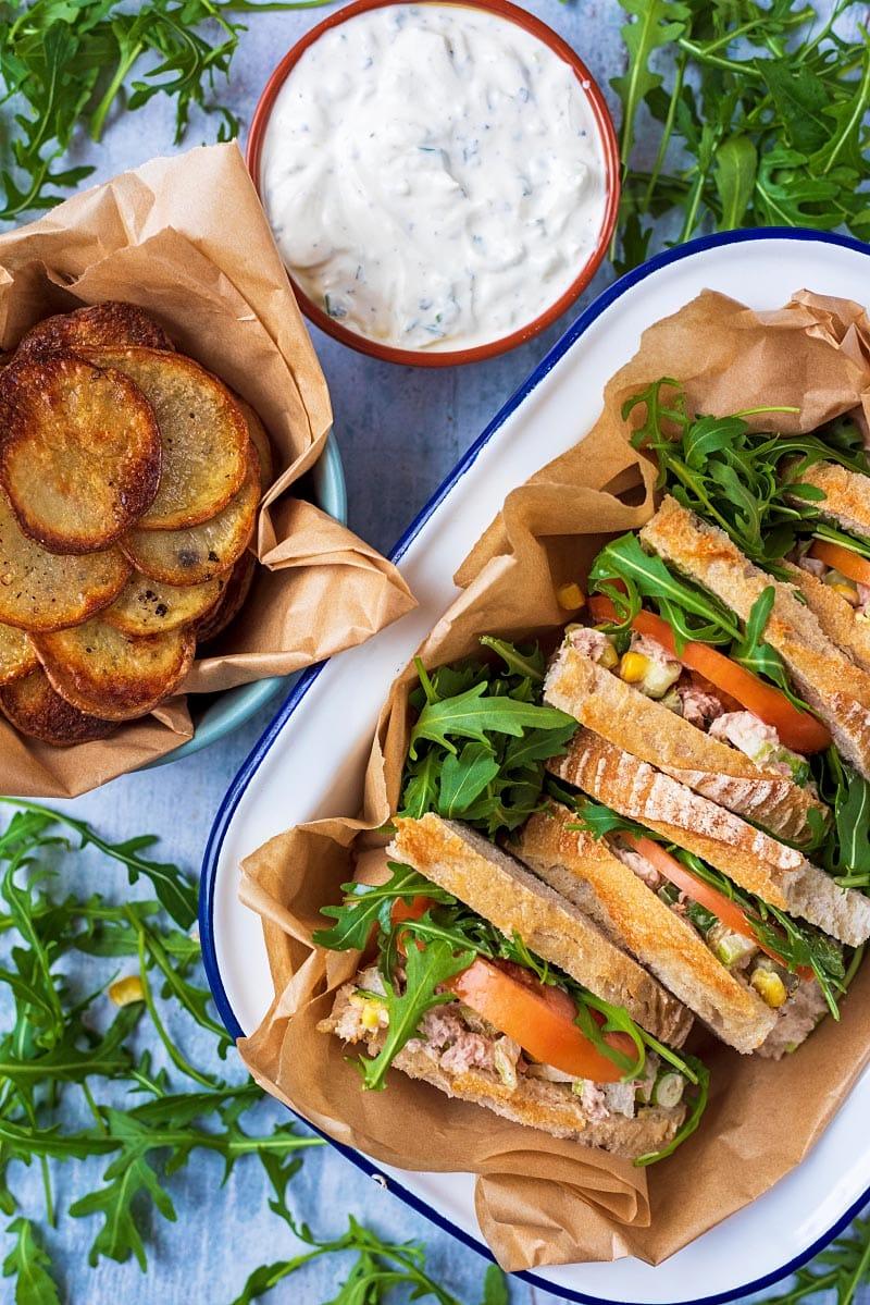 A serving dish containing tuna sandwiches next to some potato chips and tzatziki