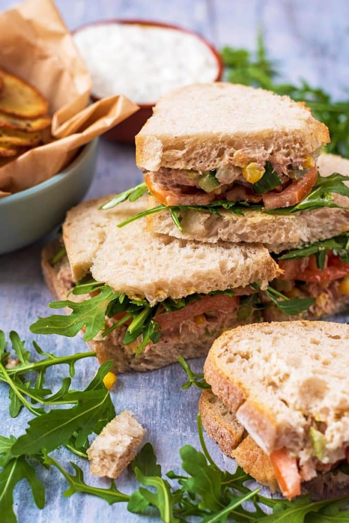 Four tuna sandwiches stacked up, surrounded by arugula and potato chips