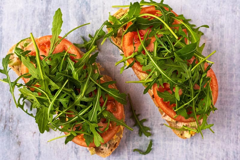 Two slices of bread topped with tuna, salad, tomatoes and arugula