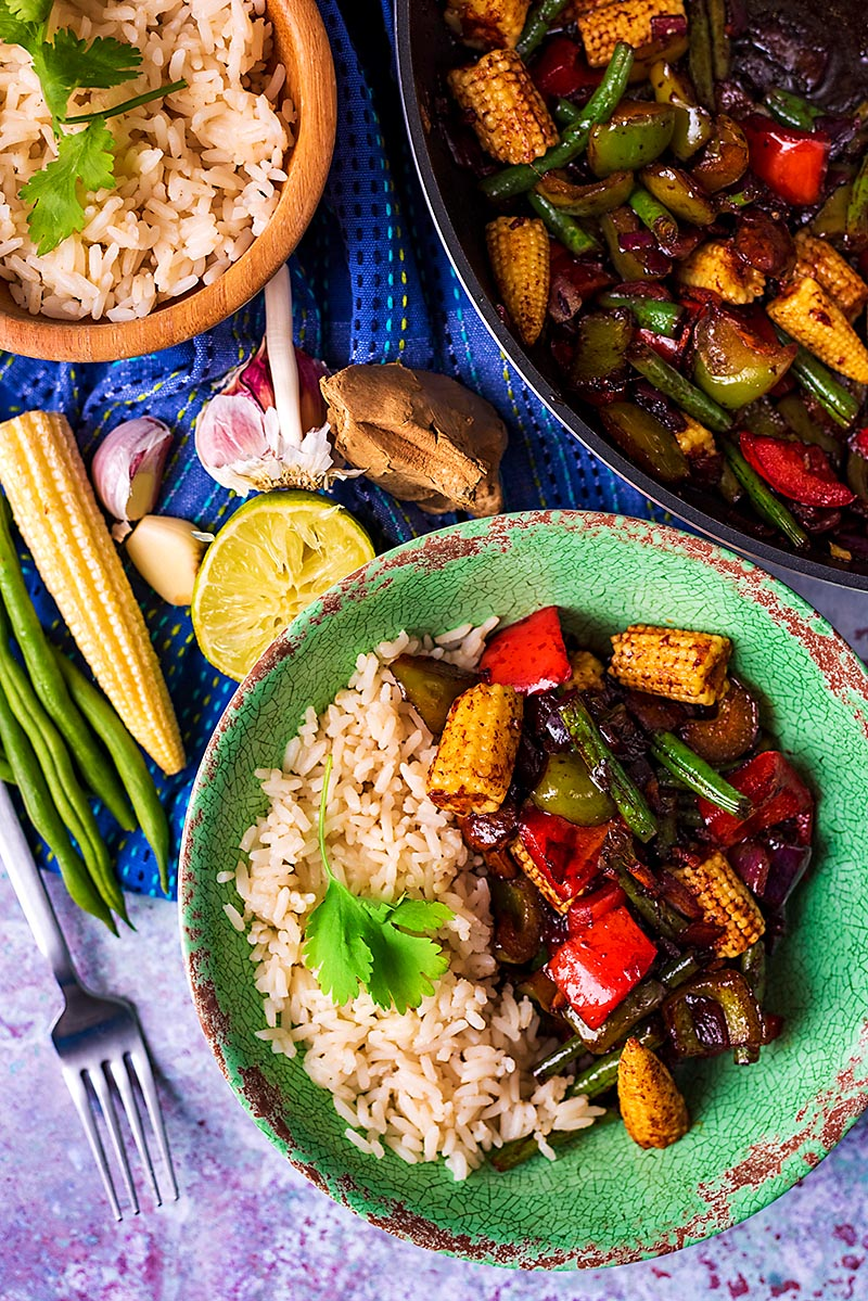10 Minute Vegetable Teriyaki in a bowl with rice next to a pan and bowl of rice