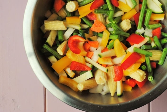 A large bowl of chopped raw vegetables