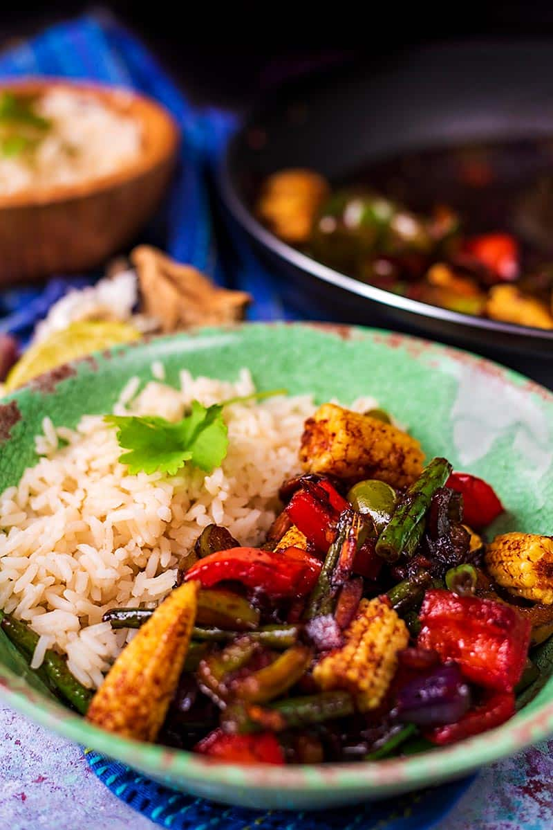 A bowl of vegetable stir-fry in front of a frying pan and a bowl of rice