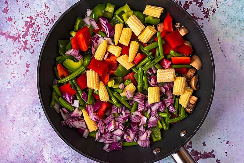 A frying pan containing chopped red onion, baby corn, green beans, bell peppers and mushrooms