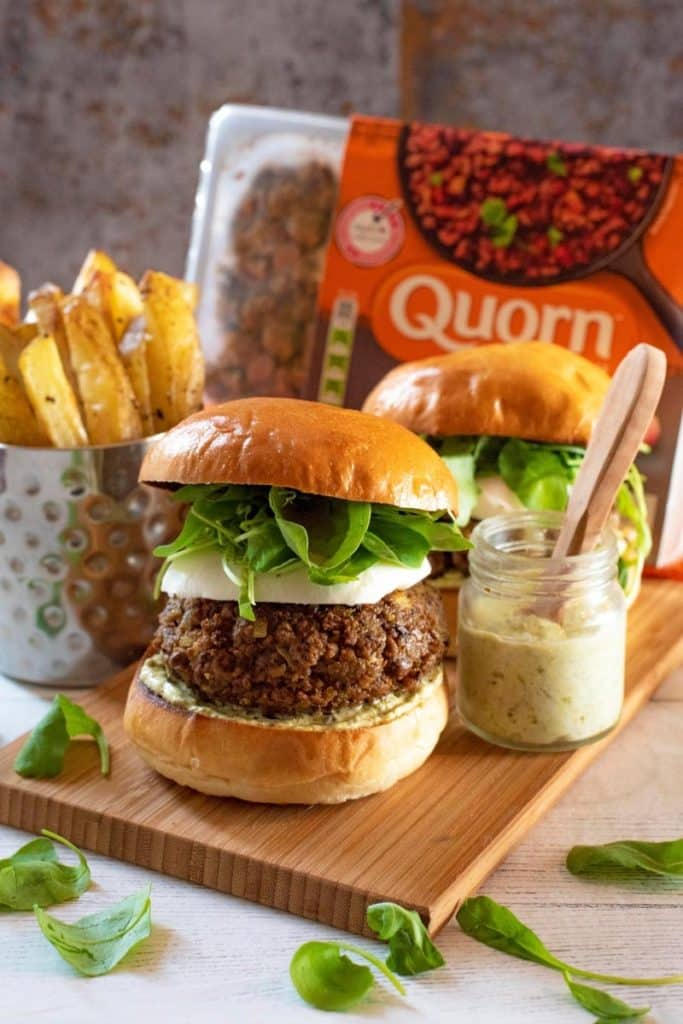 Two Quorn Pesto Burgers sat on a wooden board, pack of quorn mince in the background