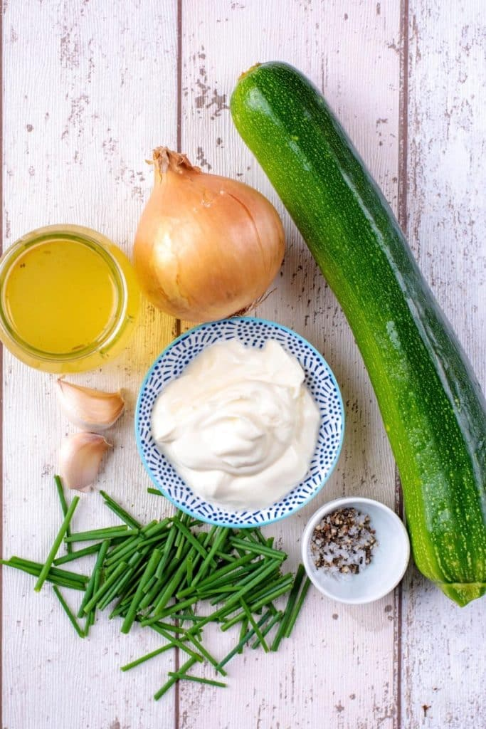 A large courgette, an onion, chives, creme fraiche, garlic cloves and stock on a wooden surface
