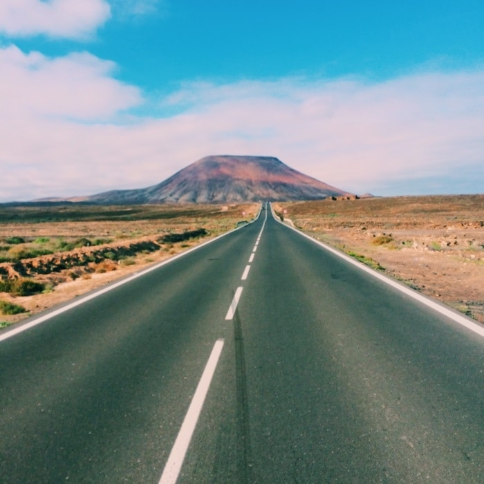 A long straight road stretching off into the distance with a mountain on the horizon