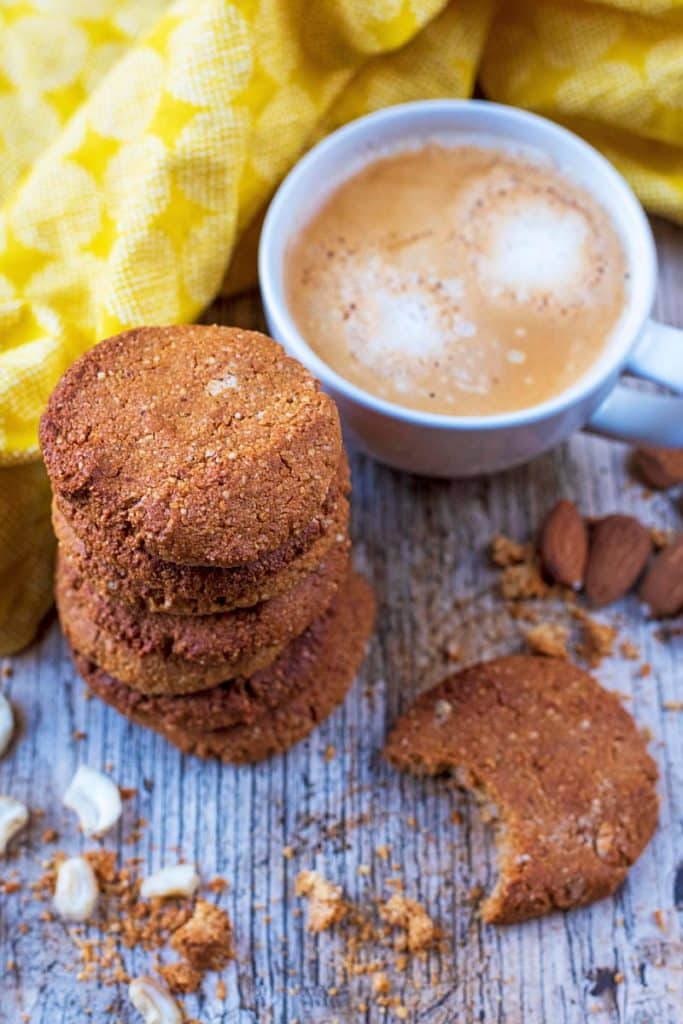 Gingernuts next to a cup of coffee and a yellow towel