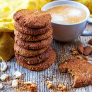 A stack od healthy gingernut biscuits in front of a cup of coffee