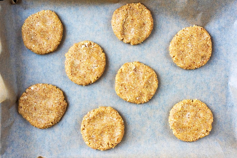 Eight uncooked biscuits on a baking tray