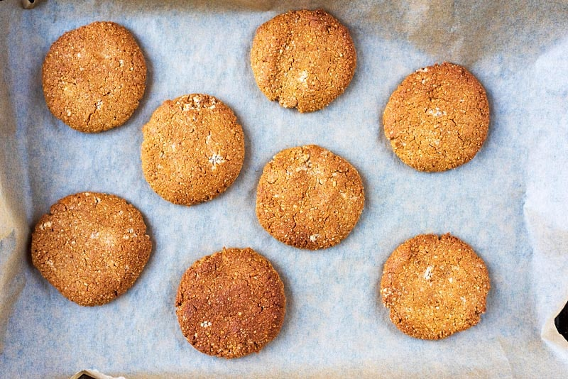 Eight golden brown biscuits on a baking tray