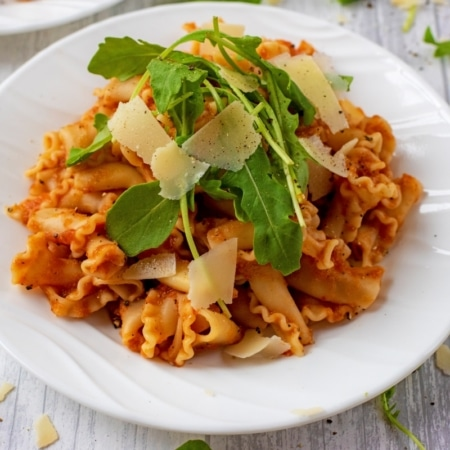 Pasta, in Slow Cooker Vegetable Pasta Sauce, topped with arugula and parmesan