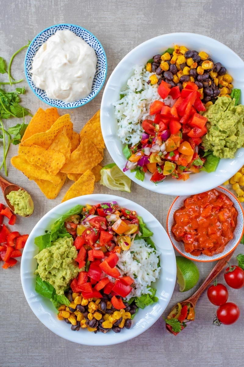 Two burrito bowls surrounded by ingredients
