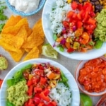 Two burrito bowls with salsa and tortilla chips