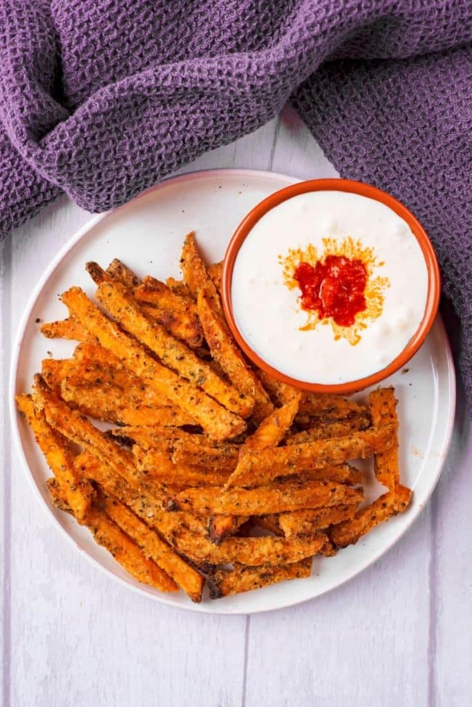 Baked Sweet Potato Fries on a white plate in front of a grey towel