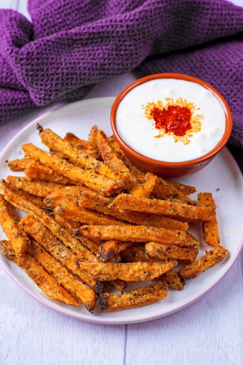 A plate of Sweet Potato Chips with a spicy yoghurt dip