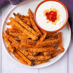Baked Sweet Potato Fries on a white plate with a small dish of dip