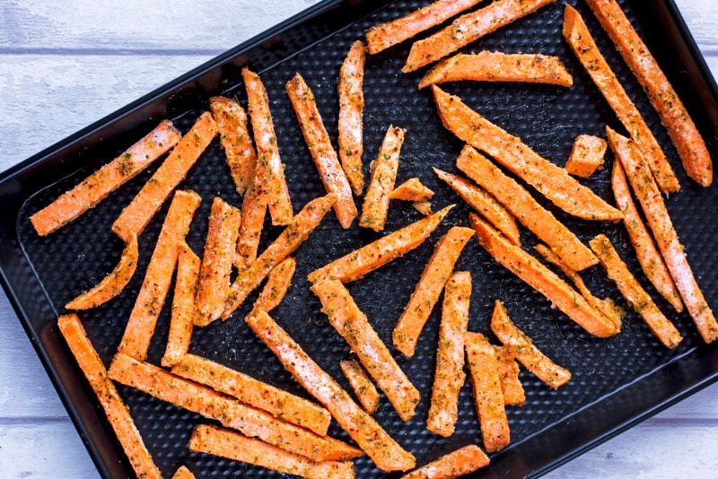 Uncooked sweet potato fries spread on a black baking tray