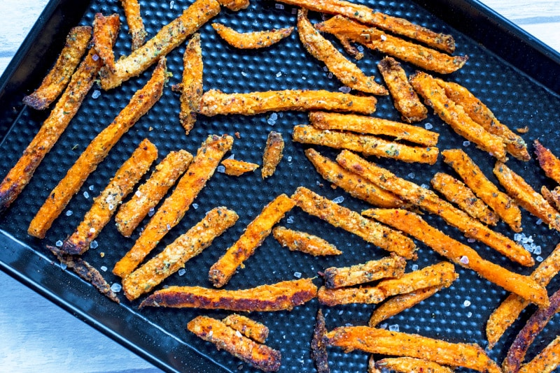 Cooked sweet potato fries on a black baking tray