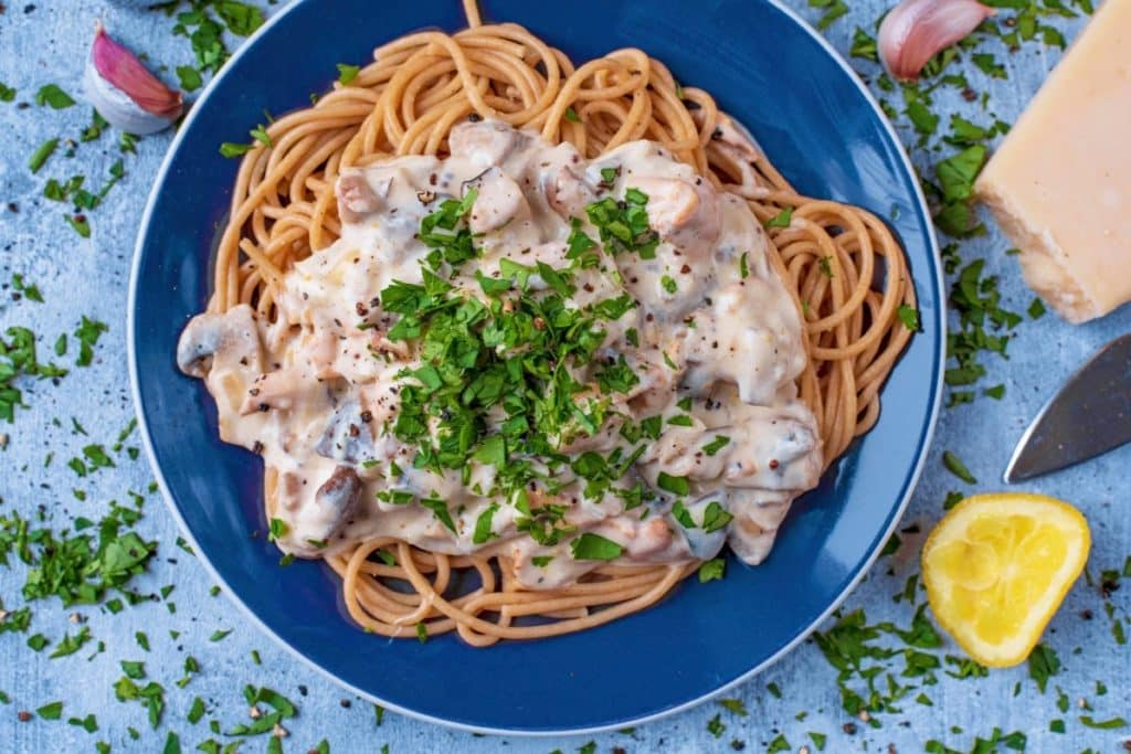 A blue plate with creamy mushroom pasta on it