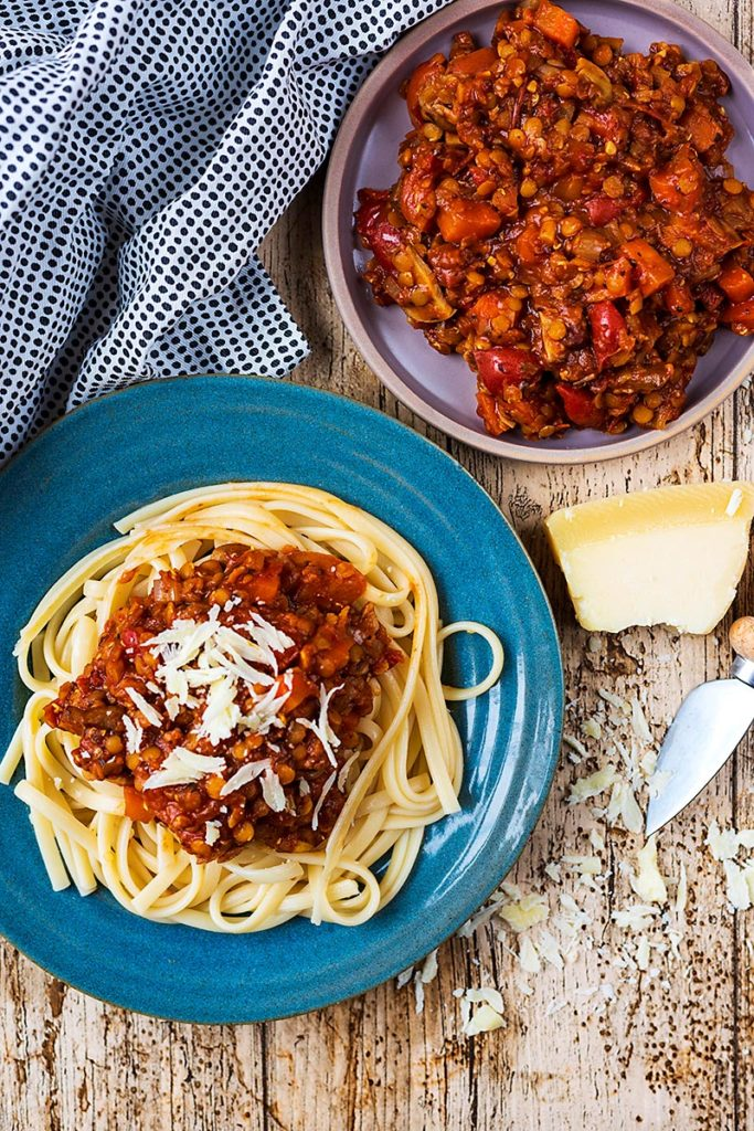 A plate of lentil bolognese and pasta topped with Parmesan shavings