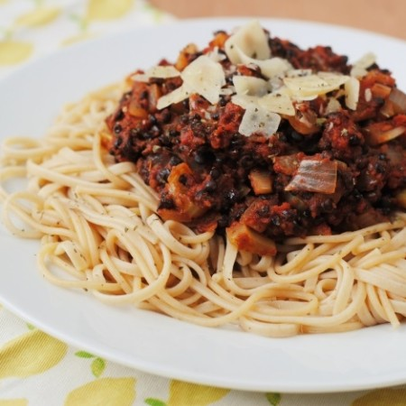 Lentil Bolognese on a bed of spaghetti on a round white plate.