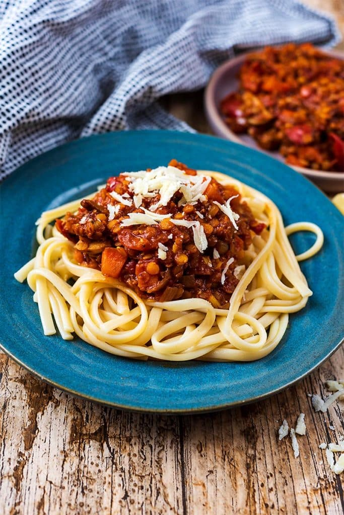 A plate of pasta and lentil bolognese in front of a spotted towel and more bolognese
