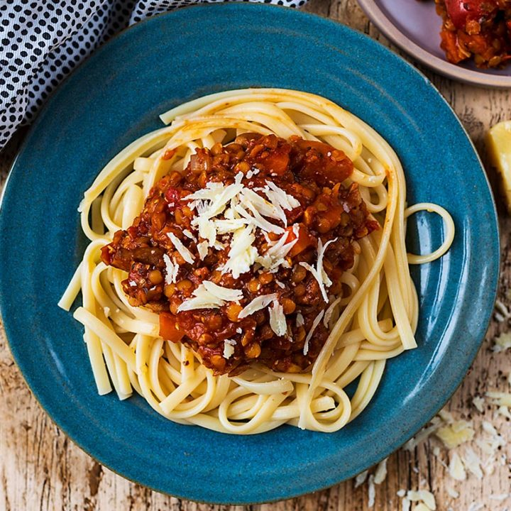 Pasta and lentil bolognese on a blue plate with cheese