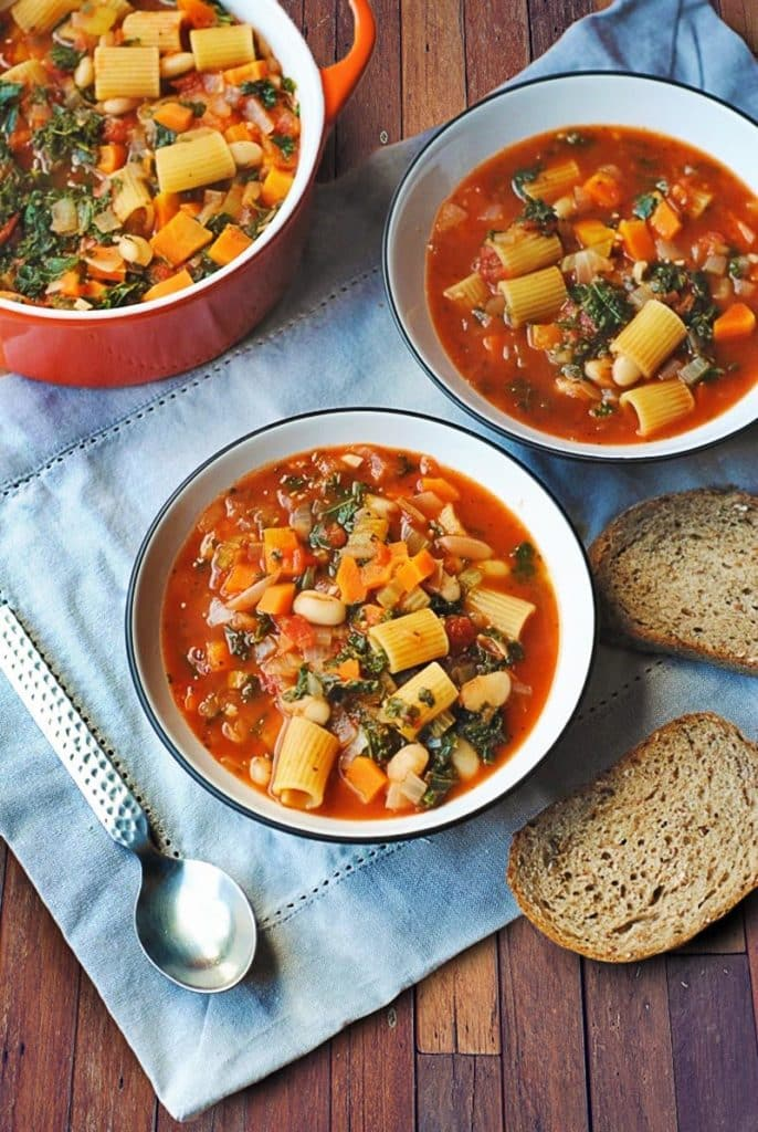 Two bowls of pasta e fagioli soup on a blue cloth next to bread and a spoon