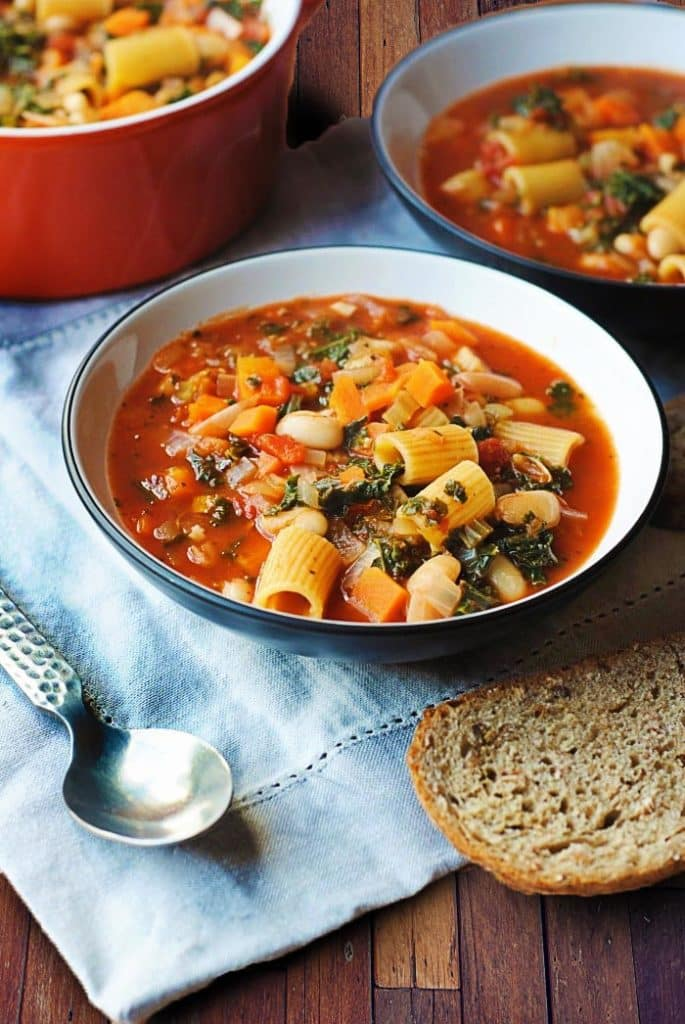 A bowl of pasta and bean soup in front of a large pot of more soup