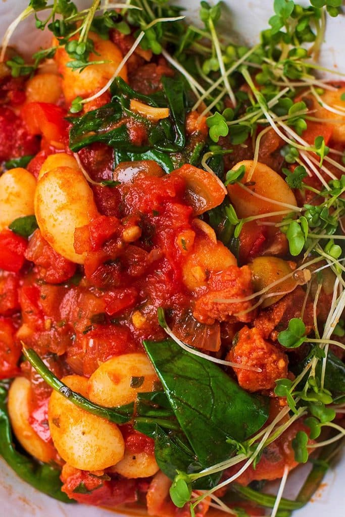 A stew of beans, chorizo and peppers mixed with wilted spinach and cress
