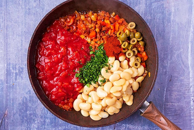 Tomatoes, butter beans, olives, chorizo, peppers, herbs and spices all cooking in a frying pan