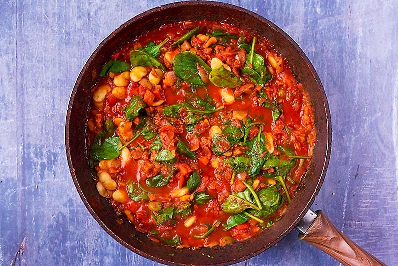 Spanish Bean Stew with wilted spinach cooking in a frying pan