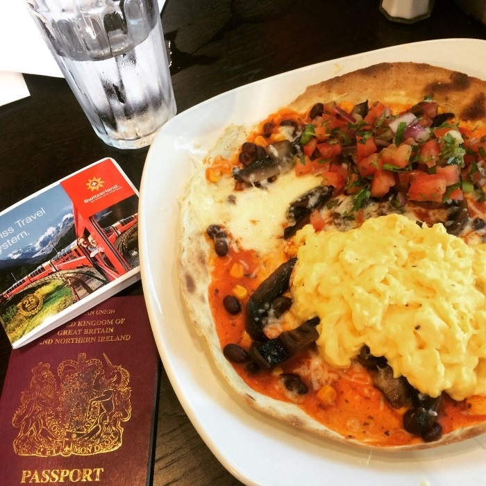 A plate of huevos rancheros next to a passport and European train pass