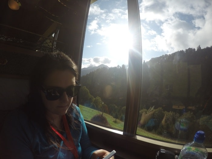 Dannii sat in a train carriage with the tree lined alps viewed through the window