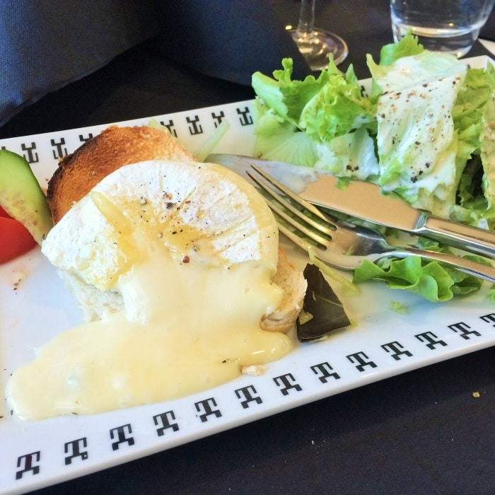 A plate of baked cheese with salad and bread