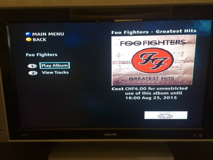 A television showing the cover of Foo Fighters Greatest Hits