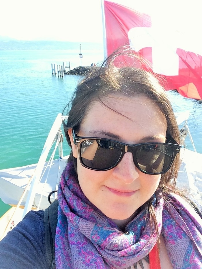Dannii taking a selfie on the deck of a boat with the Swiss flag behind her