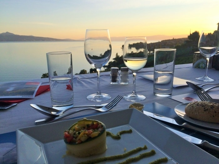 Plates, cutlery and glasses of wine and water on a table overlooking Lake Geneva