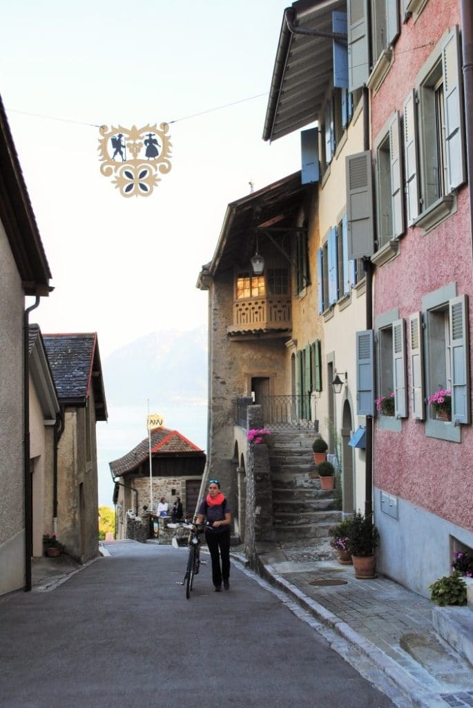 A woman walking with a bicycle up a hilly Swiss street