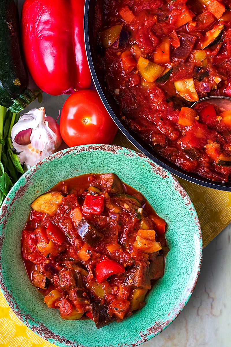 A bowl of ratatouille next to a pan of more ratatouille and some vegetables