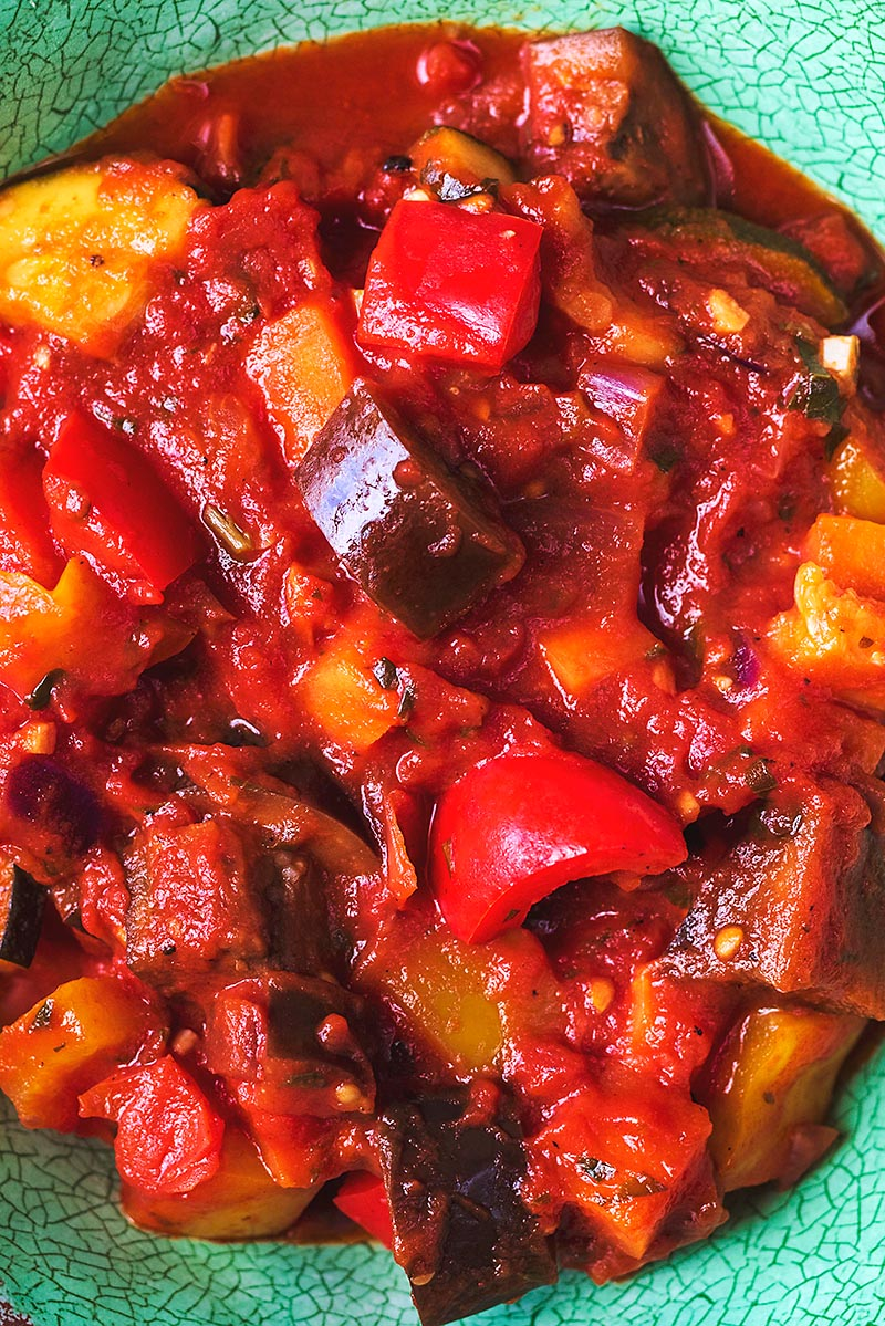 A dish of ratatouille containing peppers, eggplant, onion, zucchini, carrot and tomatoes
