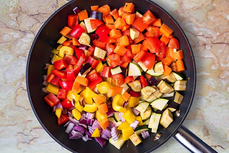 A frying pan with various chopped vegetables cooking in it