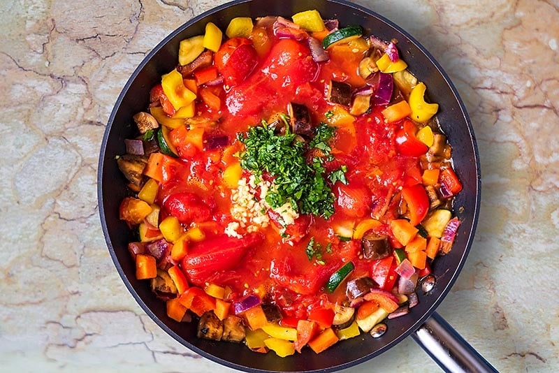 Chopped vegetables, plum tomatoes, chopped herbs and crushed garlic all cooking in a frying pan
