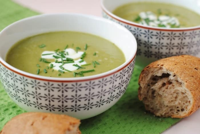 Two bowls of Asparagus Soup next two chunks of French bread