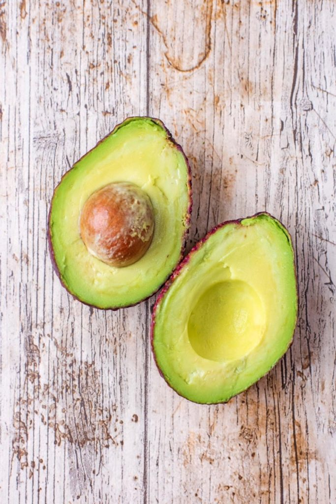 An avocado cut in half on a wooden surface